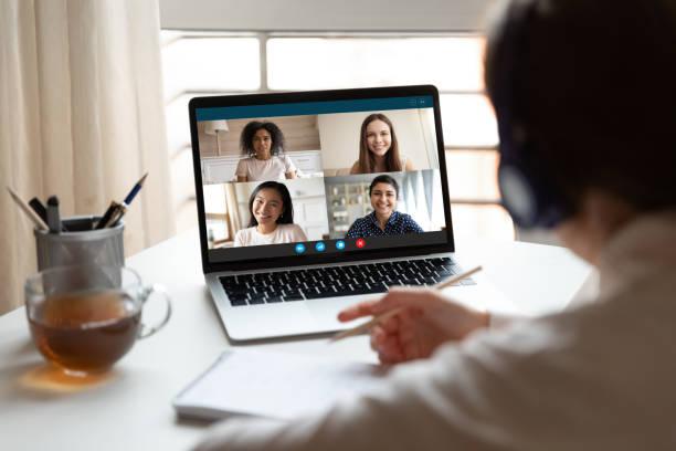 Frau studiert zu Hause mit multirassischen Studenten via Videokonferenz – Foto