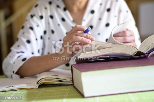 Woman studying for her assignment, flipping pages of a book while taking notes,