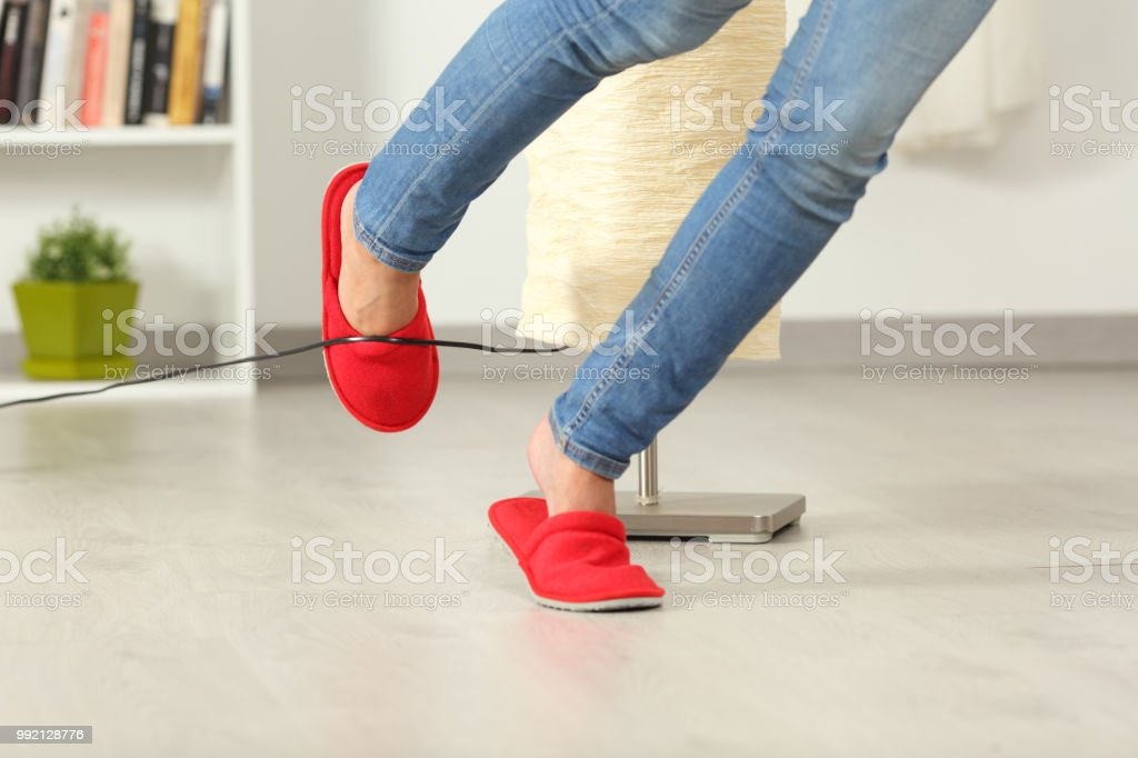 Woman stumbling with an electrical cord at home stock photo
