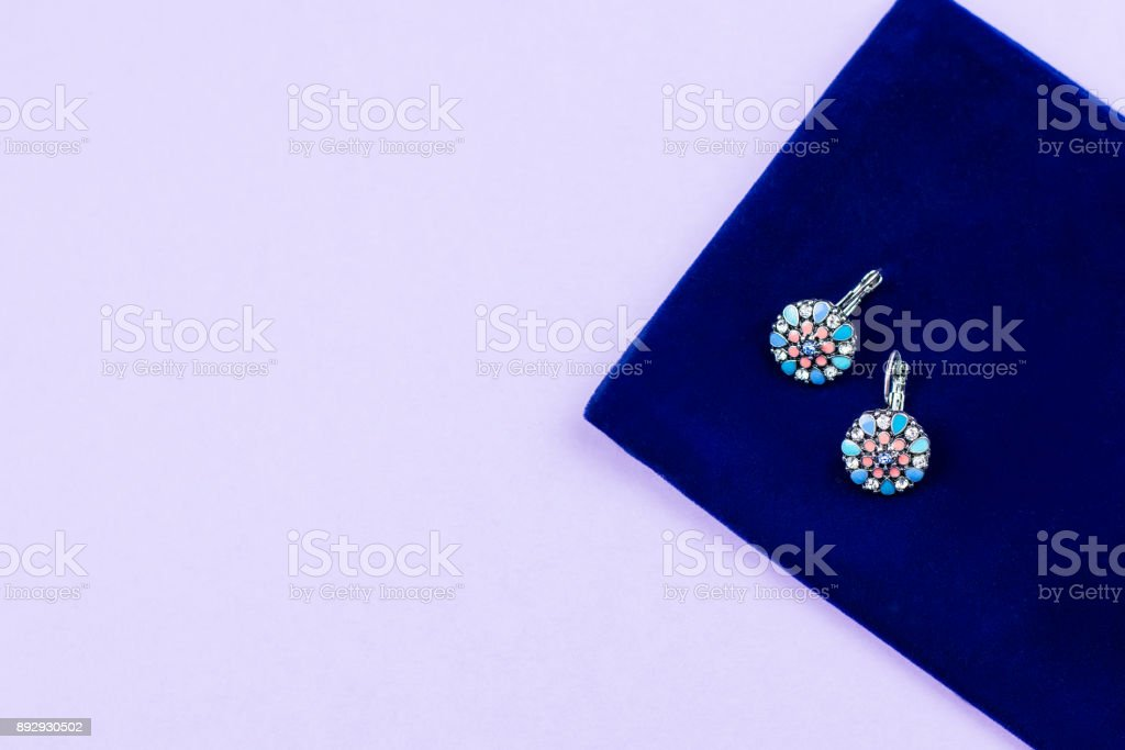 Woman stylish earrings in pink and blue colors on pastel background. stock photo