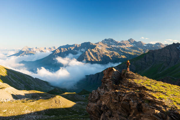Woman success concept looking at view from mountain top, dramatic landscape clouds over the valley, sunset clear blue sky. Summer activity fitness wellbeing freedom loneliness. stock photo