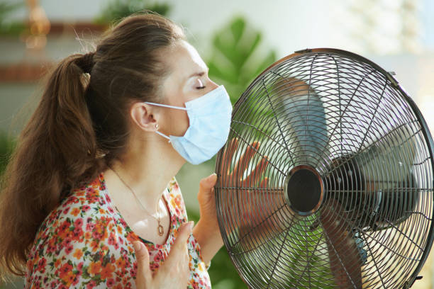 woman suffer from heat at modern home in sunny hot summer day stock photo