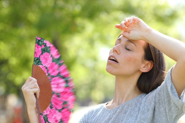Woman suffering a heat stroke in a warm summer day stock photo