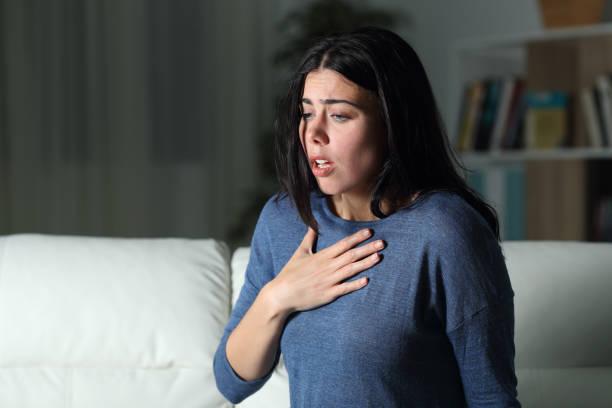 mujer sufriendo un ataque de ansiedad solo en la noche - ansiedad fotografías e imágenes de stock