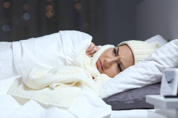 Woman suffering cold in a bed in winter stock photo