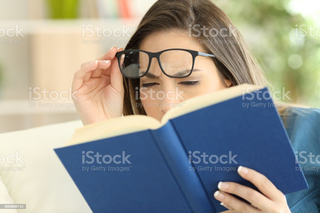 Woman suffering eyestrain reading a book stock photo