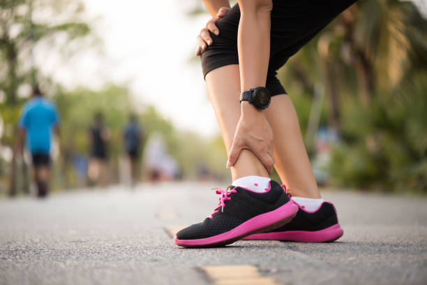 woman suffering from an ankle injury while exercising. running sport injury concept. - slogatura foto e immagini stock