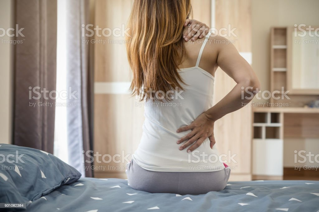 Woman suffering from back ache on the bed stock photo