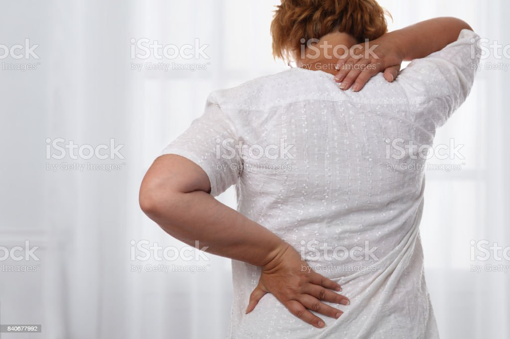 Woman suffering from back and neck pain. Chiropractic, osteopathy, Physiotherapy. Alternative medicine, pain relief concept. stock photo