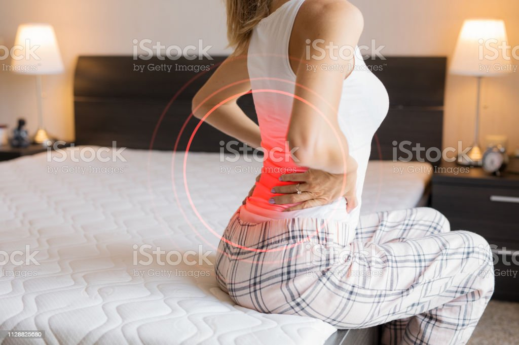 Woman suffering from back pain because of uncomfortable mattress - Royalty-free Backache Stock Photo