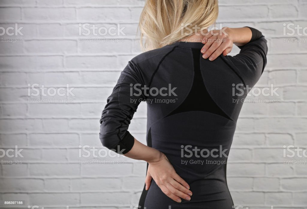 Woman suffering from back pain. Sport exercising injury, Muscle spasm, Pain relief , chiropractic concept. stock photo