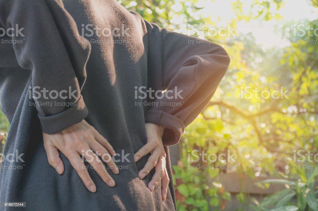 Eine Frau, die unter Rückenschmerzen leiden, Ausgabe Rückenmarksverletzung und Muskel Problem im Freien. – Foto