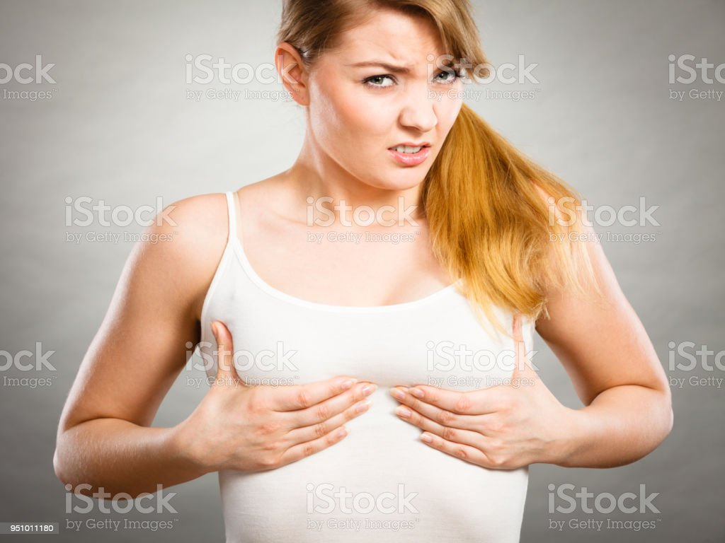 Woman suffering from breast pain - Stock image .