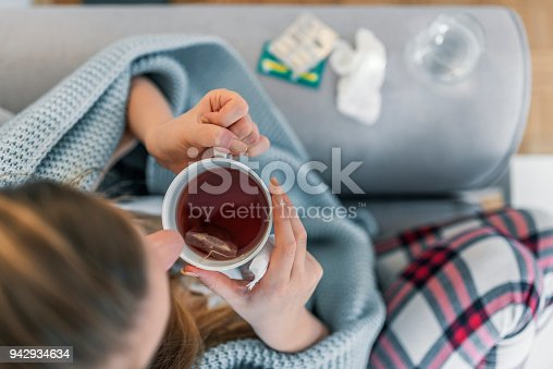 Upper view of Sick woman with a headache sitting on a sofa at home wrapped in blanket during the day. Sickness, seasonal virus problem concept. Woman being sick having flu lying on sofa.