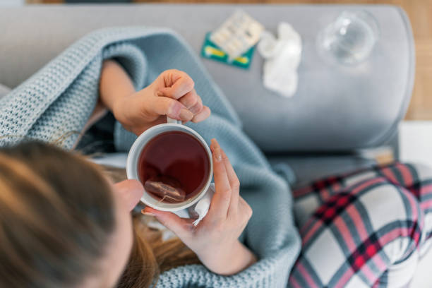Woman suffering from cold flu Upper view of Sick woman with a headache sitting on a sofa at home wrapped in blanket during the day. Sickness, seasonal virus problem concept. Woman being sick having flu lying on sofa. cold virus stock pictures, royalty-free photos & images