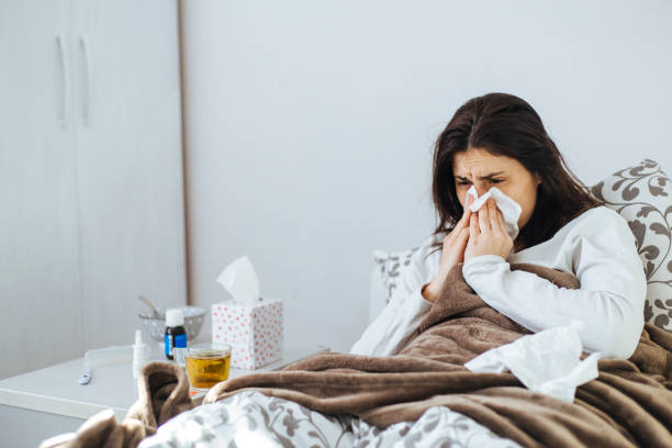 Woman Suffering From Cold Lying In Bed With Tissue stock photo