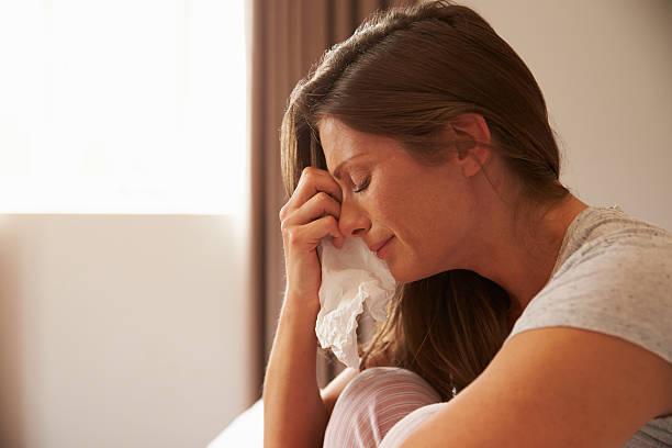 frau, die unter depressionen sitzen auf bett und weinen - träne stock-fotos und bilder