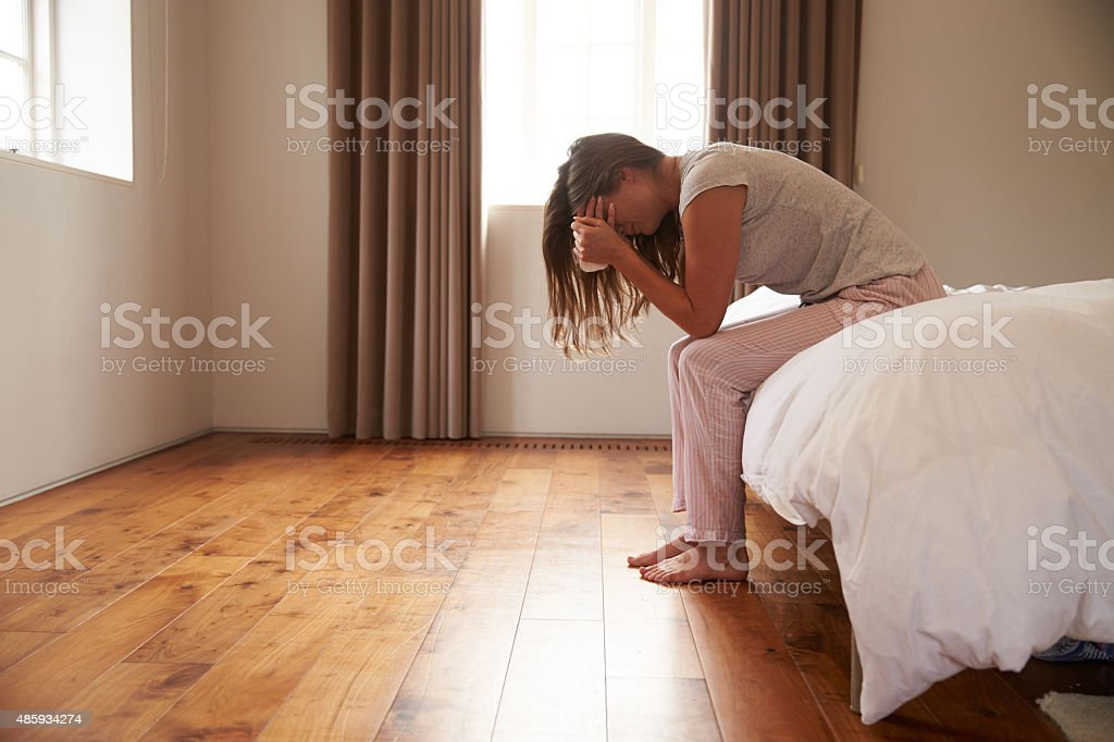 Woman Suffering From Depression Sitting On Bed And Crying stock photo
