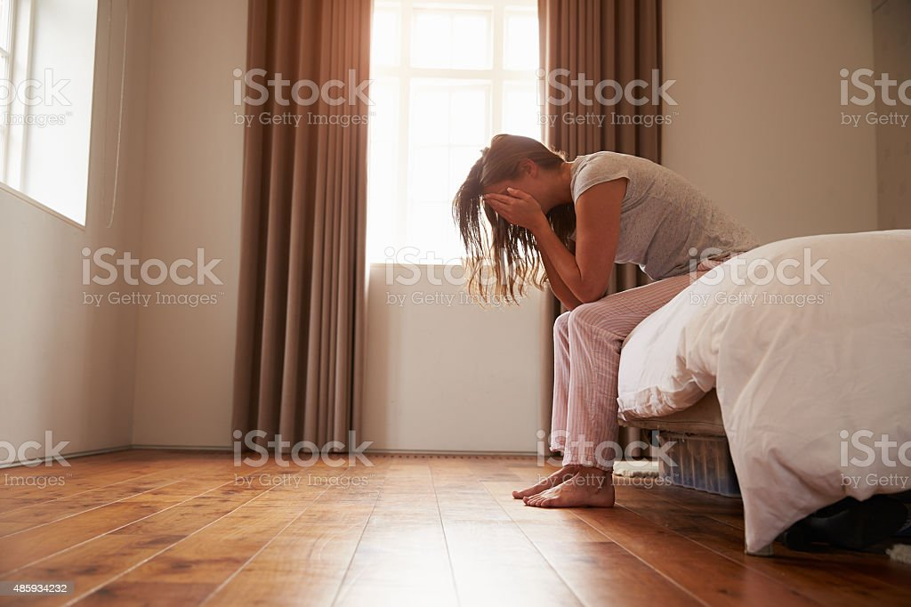Woman Suffering From Depression Sitting On Bed In Pajamas stock photo