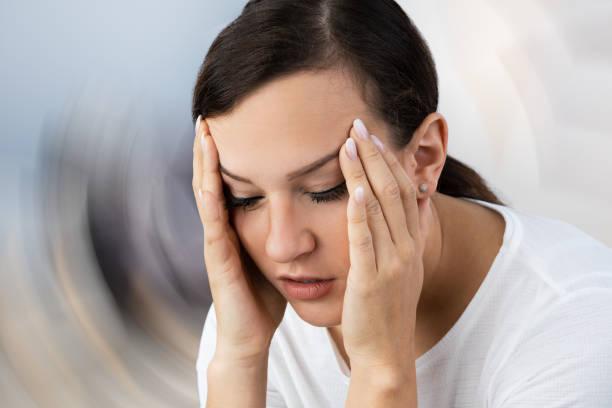 frau leidet unter kopfschmerzen schwindel - höhenangst stock-fotos und bilder