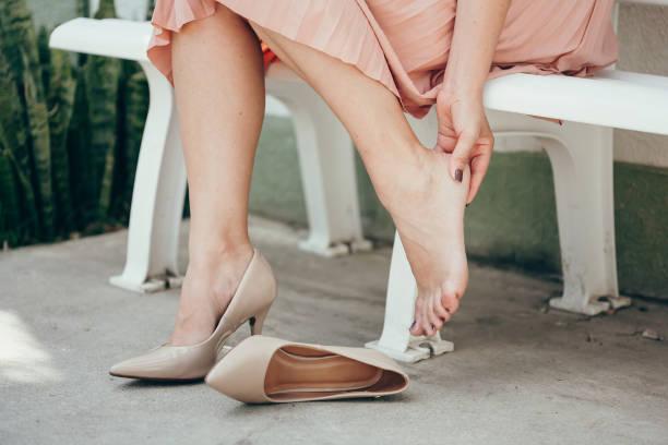 Frau leidet unter Beinschmerzen im Freien wegen unbequemer Schuhe. – Foto