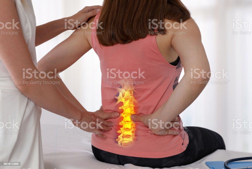 Woman suffering from low back during medical exam. Chiropractic, osteopathy, Physiotherapy. Alternative medicine, pain relief concept. stock photo