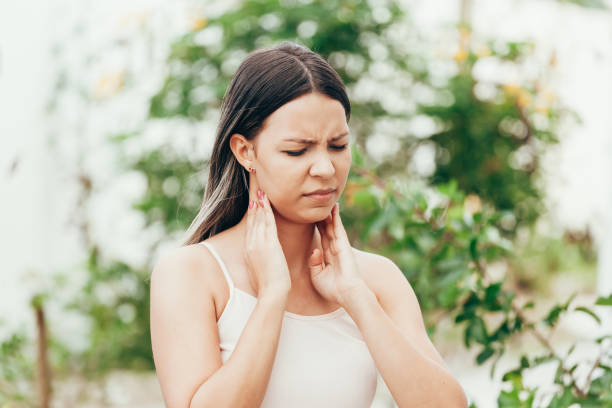 Woman suffering from sore throat in the garden Woman suffering from sore throat in the garden throat stock pictures, royalty-free photos & images