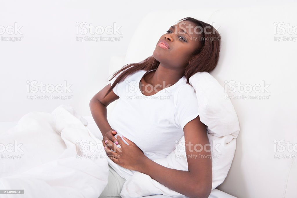 Woman Suffering From Stomachache In Bed stock photo