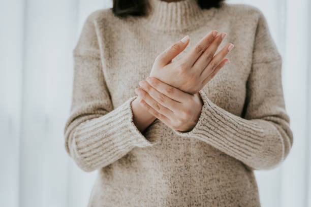 Woman suffering from wrist pain Cropped shot of woman in sweater holding her wrist pain arthritis stock pictures, royalty-free photos & images