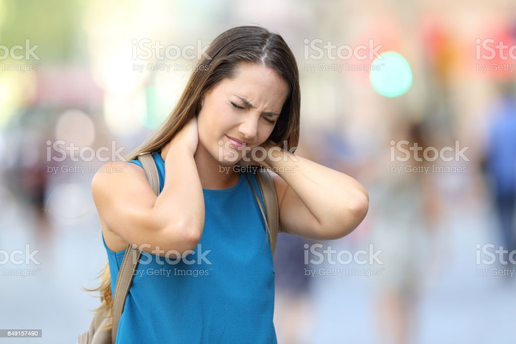 Woman suffering neck ache on the street stock photo