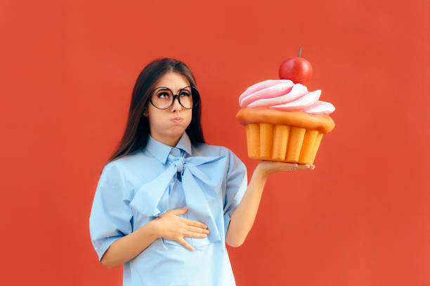 woman suffering stomach ache after eating too much cupcake - full stock photos and pictures