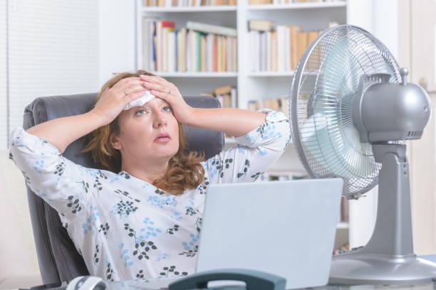Frau leidet unter Hitze im Büro oder zu Hause – Foto