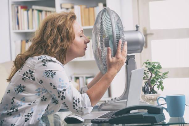 mujer sufre de calor en la oficina o en casa - calor fotografías e imágenes de stock