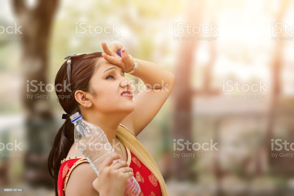Woman suffers from heat of strong sunlight, Blur background stock photo