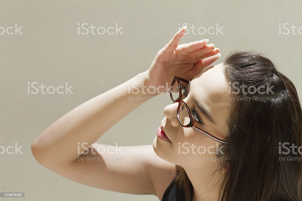 woman suffers from heat of strong sunlight, plain background stock photo