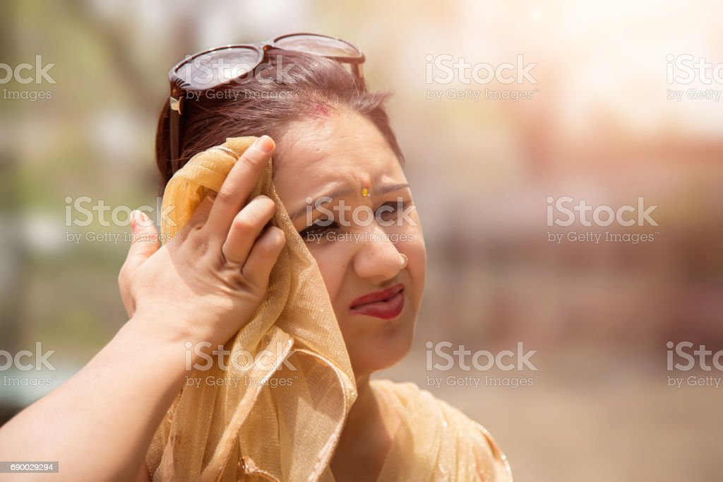 Woman suffers from heat of strong sunlight,Blur background stock photo