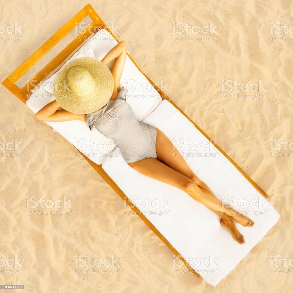 Woman sun bathing at the beach stock photo