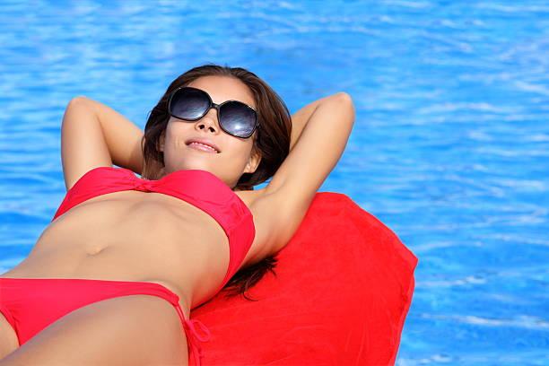 Woman sunbathing by pool stock photo