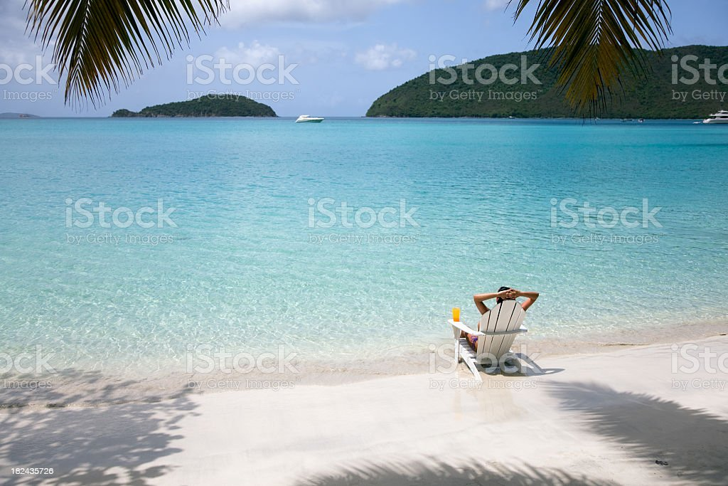 woman sunbathing in a chair at the beach royalty-free stock photo
