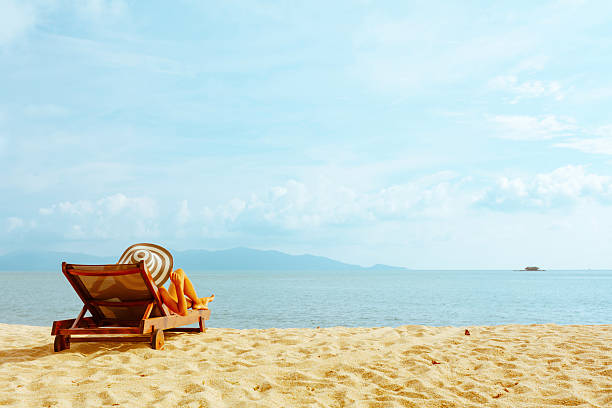 woman sunbathing in beach chair stock photo