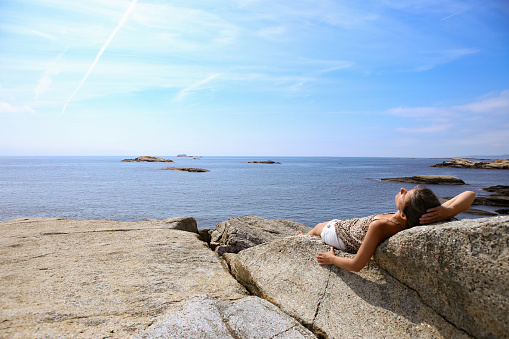 Woman sunbathing on a rock in The End of the Earth in Norway.