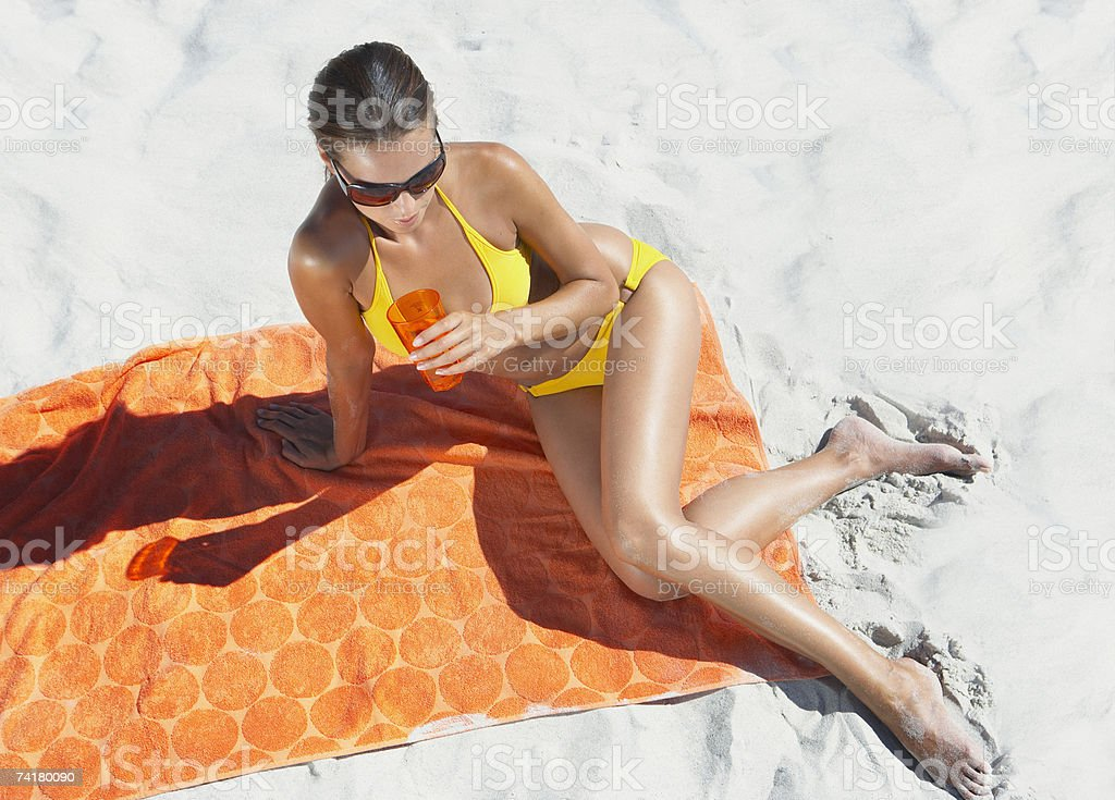 Woman sunbathing on beach towel in sand with beverage stock photo