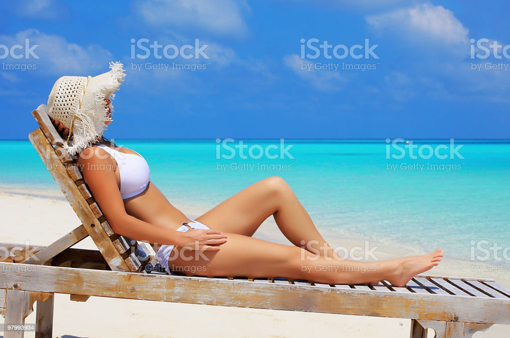 Woman sunbathing on deck chair at the beach. royalty-free stock photo