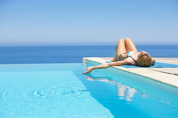 Woman sunbathing on deck with infinity pool  infinity pool stock pictures, royalty-free photos & images