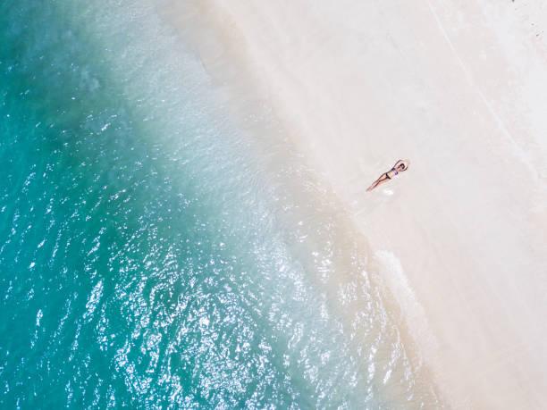 vrouw zonnebaden op het strand - lombok stockfoto's en -beelden