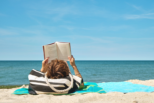 Caucasian woman lying on the beach reading a book on bright summer day