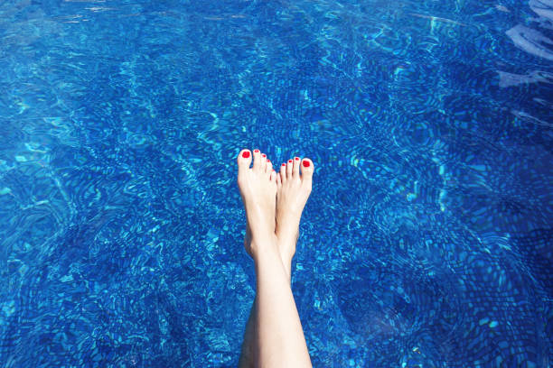 Woman sunbathing with legs in swimming pool in the summer time or exotic holiday stock photo