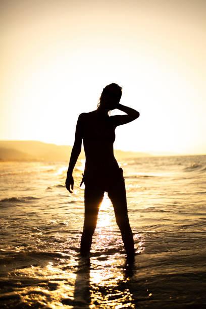 Woman sunset at beach stock photo