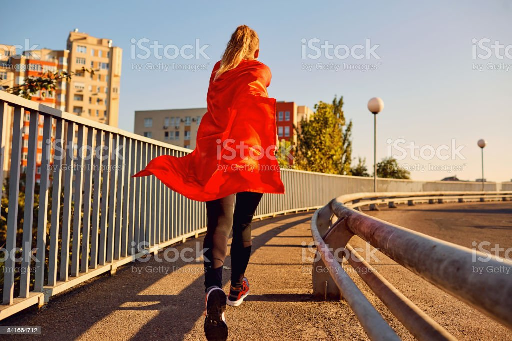 Woman super-hero runner in a red raincoat jogs. stock photo