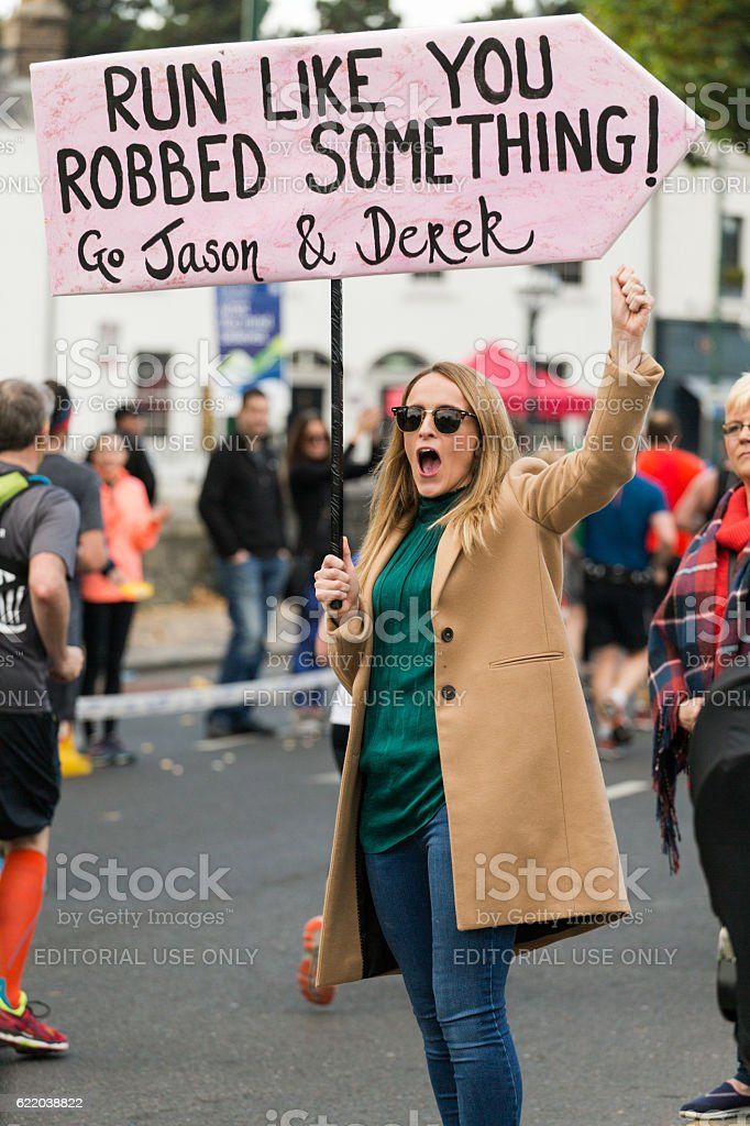 Woman supporting friends in marathon stock photo